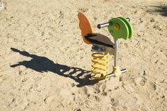 Bird swing spring rider. In sandy playground Stock Photos