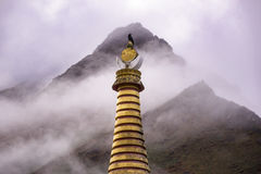 Bird on top of Tengboche Stupa with cloudy mountain behide. Morning time. After raining. Stock Photography