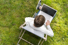 Bird view on man typing on his laptop computer outdoors. Bird view on young adult smart casual sitting on a chair with his large laptop computer. He is typing Stock Images