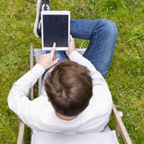 Bird view on unrecognizable person with digital tablet sitting Royalty Free Stock Photography
