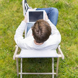 Bird view on unrecognizable person with digital tablet sitting o Stock Image