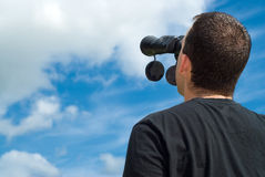 Bird Watcher. Low angle view of a bird watcher using binoculars with some blue sky and clouds behind him Stock Image