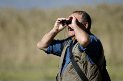Bird Watcher. A senior hiker and bird watcher is searching for birds with binoculars Royalty Free Stock Image