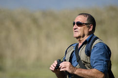 Bird Watcher. A senior hiker and bird watcher is searching for birds with binoculars Stock Photos