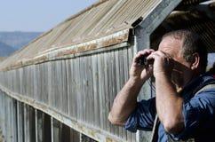 Bird Watcher. A senior hiker and bird watcher is searching for birds with binoculars Stock Photography