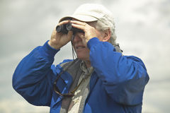 Bird watcher with binoculars in spring grasslands and mountains, Centennial Valley, near Lakeview, MT