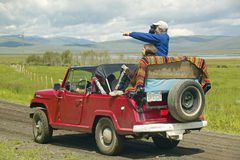 Bird watchers and red jeep in spring grasslands and mountains in Centennial Valley, Lakeview MT Stock Photography