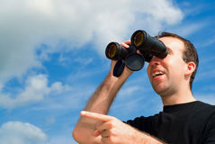 Bird Watching. A man bird watching with a set of binoculars and is pointing with his finger Stock Image