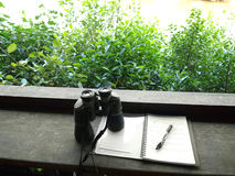 Bird watching hobby. A conceptual picture of a pair of binoculars placed on some birdwatching notes taken by young child.  Location is inside bird watching hide Stock Photo