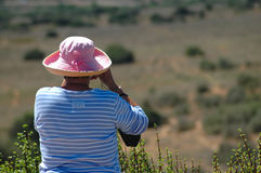 Bird watching tourist. An elderly caucasian senior woman tourist with a pink hat and a blue and white shirt bird watching and spotting wildlife in nature through Stock Image