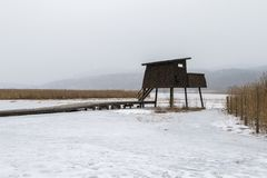 Bird watching tower in snowy weather, in Skien, Norway,. Bird watching tower in Borsesjo, snow in the air and snow and ice coverint the lake and ground. Skien royalty free stock photography