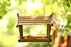 Bird wooden creative feeder as a part of garden design element. Close up photo on green summer background royalty free stock images