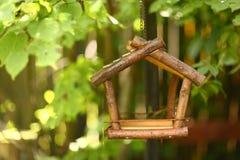 Bird wooden creative feeder as a part of garden design element. Close up photo on green summer background stock photos