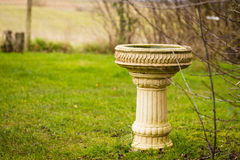 Birdbath in the countryside. Large stone ornate birdbath in the countryside Stock Photography