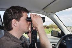 Birder with binoculars. Man looking through binoculars in car stock image