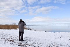 Birder by a coast in winter season. Birder watching at birds by the coast in winter season at the swedish island Oland stock photo