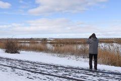 Birder in winter season. Birdwatcher watching in a wetland in winter season royalty free stock photo