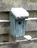 Birdhouse covert in snow. Hanging on a wooden fence Royalty Free Stock Photo