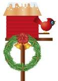 Birdhouse di Natale con il cardinale e la corona Immagini Stock