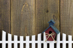 Birdhouse hanging on white picket fence Stock Image