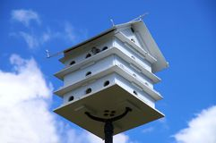 Birdhouse. High-standing birdhouse with a sparrow on a blue sky background Royalty Free Stock Photos