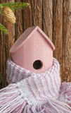 Birdhouse, house insulation. Birdhouse wrapped in a warm woollen scarf, insulated for winter. Home insulation concept royalty free stock image