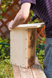 Birdhouse, a man assembling wooden parts Stock Photos
