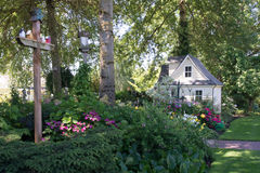 Birdhouse and Playhouse. A charming playhouse sits at the edge of a shaded perennial garden.with birdhouses in the foreground Stock Photo