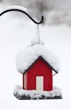 Birdhouse rojo en la nieve blanca foto de archivo