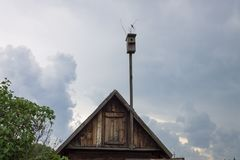 Birdhouse on the roof of a house against a cloudy sky background royalty free stock photos