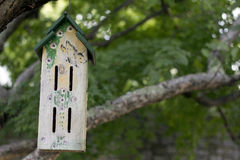 Birdhouse in a tree. A beautiful birdhouse, with a painting of a butterfly and flowers, hanging in a tree stock images