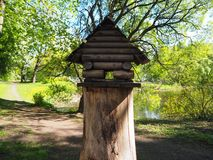 A birdhouse on a tree stump, a wooden feeder for birds royalty free stock image