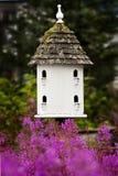 Birdhouse und rosafarbene Blumen Lizenzfreies Stockbild