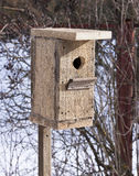 Birdhouse from unplaned boards. Stock Photos