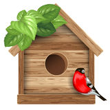 Birdhouse. Wooden birdhouse with bird bullfinch and leaves Stock Photography