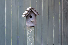 Birdhouse by Wooden Fence Stock Images