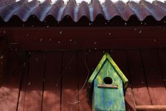 Birdhouse And Droplets. A birdhouse on the wooden house and droplets running down stock photo