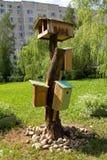 Birdhouses και ένας τροφοδότης πουλιών στον κήπο στο προαύλιο ενός multi-storey κτηρίου στοκ εικόνες