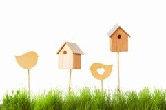Birdhouses и деревянная птица на предпосылке зеленой травы Стоковое Изображение