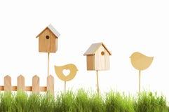 Birdhouses и деревянная птица на предпосылке зеленой травы Стоковые Фото