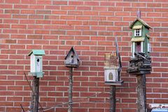 4 birdhouses with brick background. On posts royalty free stock images
