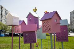 Birdhouses are colored on the background of houses and blue sky. royalty free stock photography