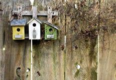 Birdhouses rústicos viejos en la cerca Imágenes de archivo libres de regalías