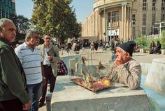 Birdman handelt die Spatzen auf gedrängter Marktstraße von Teheran Stockbilder