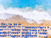 Birds eye view of a beach with big waves, sunbeds and umbrellas Stock Images