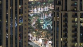 Birds eye view of Dubai skyline timelapse and rush hour traffic in downtown at night. Road with palms between houses stock footage