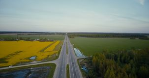 Freeway in flatland with forest and canola field. Aerial drone 4K rotating shot. Agricultural crops industry logistics. Birds eye view freeway in flatland with stock video