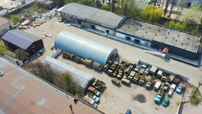Birds eye view of an old storage rooms with broken cars and trucks. Aerial. Footage stock video