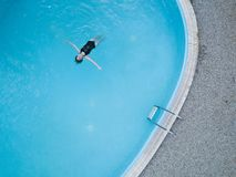 Birds eye view of an outdoor pool and a long hair black swimsuit girl swims in the water royalty free stock images