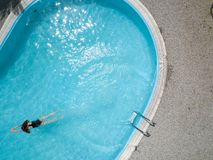 Birds eye view of an outdoor pool and a long hair black swimsuit girl swims in the water stock photography